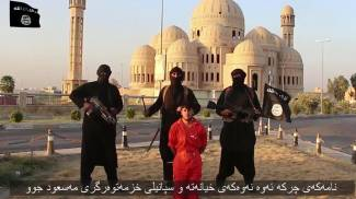 I momenti precedenti alla decapitazione di un prigioniero curdo a Mosul (Ansa)