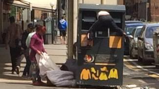 Rom, gambe all'aria, ruba gli abiti usati dal cassonetto