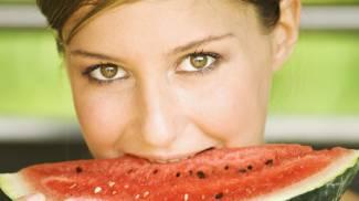 Estate, una ragazza mangia una fresca anguria